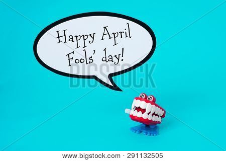 a funny denture and the text happy april fools day in a speech balloon, on a blue background
