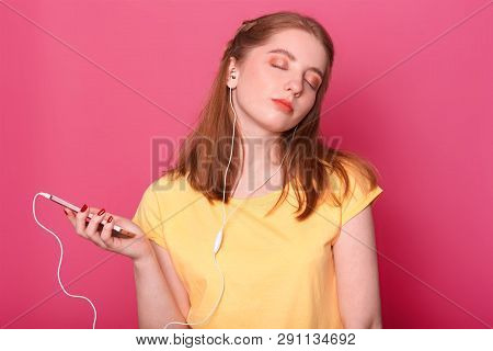 Dreamy Female With Pensive Expression And Closeed Eyes, Has Modern Headphones, Listen To Music, Spen