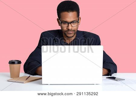 Close Up Portrait Of Dark Skinned Male Wears Black Suit, Works Online With Lap Top, African American