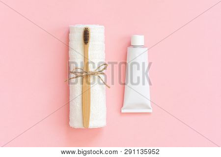 Natural Eco-friendly Bamboo Brush On White Towel And Toothpaste Tube. Set For Washing On Paper Pink