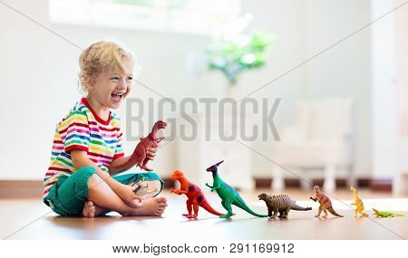 Child Playing With Toy Dinosaurs. Kids Toys.