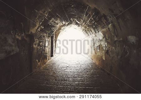 View To Some Old Passageway With Stone Walls Of Archeway, Old Pavement And Bright Light At The End O