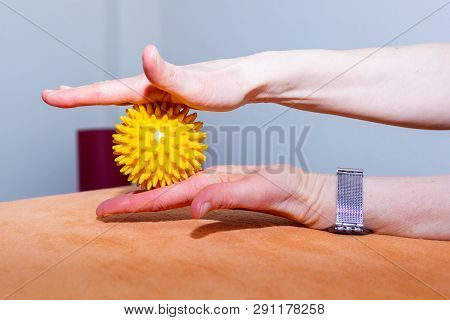 A Woman Is Exercising With A Massage Ball