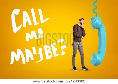 Young Man In Casual Clothes Standing In Half-turn, One Hand On Chin, Near Big Cyan Phone Receiver On