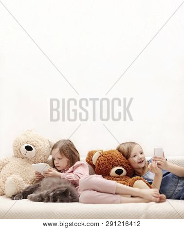 Two Little Girls (sisters 7 And 8 Years Old) Are Watching An E-book And A Smartphone At Home On The