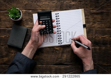 Business man is counting money on a calculator and is writing a sum in a notebook with a blank pages. Accountant. poster
