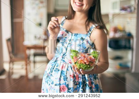 Close-up Happy Pregnant Woman Standing In Kitchen, Keeping Plate With Vegetables And Smiling. Young
