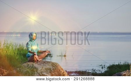 Beautiful Peaceful Woman Sits In A Pose Of A Half Lotus Practicing Yoga Meditation, Blue Summer Sky,