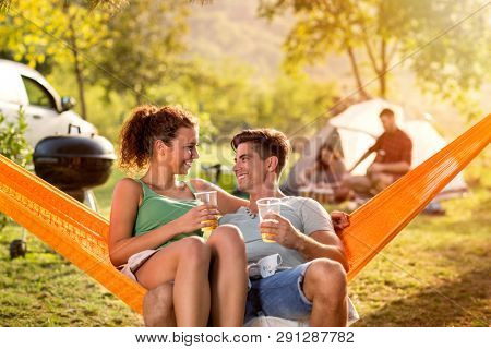 Smiling love couple drinking beer and enjoying in hammock chair on camping trip