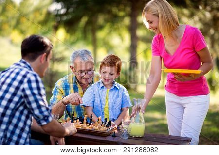 happy family relaxing playing chess in the park