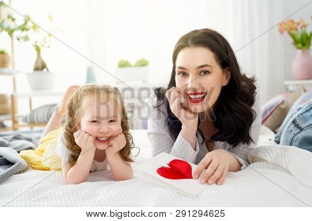 Happy mother's day! Child daughter is congratulating mom and giving her postcard and gift. Mum and girl smiling and hugging. Family holiday and togetherness.