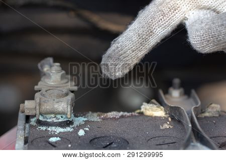 Mechanic Hand Pointing Car Battery Terminalin A Garage. Old Battery Corrosion Deteriorate Leaking