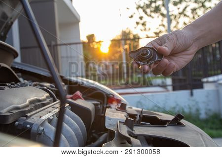 Mechanic Man Checking Car Engine Radiator Cooling Tank Water Level. Hand Holding Radiator Coolant Ca