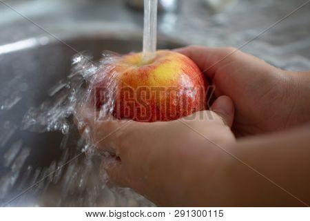 Female Hands Washing Red Appleunder Water Stream In Kitchen Metallic Sink,closeup. Healthy Woman E