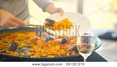 Paella traditional Spanish food. Person putts seafood paella from the fry pan to plate. Paella with with mussels, king prawns, langoustine and squids. Person cooking paella. Family Dinner