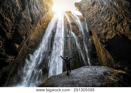 poster of Traveler stunned by Gljufrabui waterfall cascade in Iceland. Located at scenic Seljalandsfoss waterfall South of Iceland, Europe. It is top beautiful destination of popular tourist travel attraction.