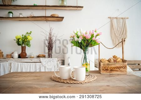 Summer Kitchen Interior In Rustic Style. Bright Kitchen With A Wooden Table. Spring Flowers And Brea