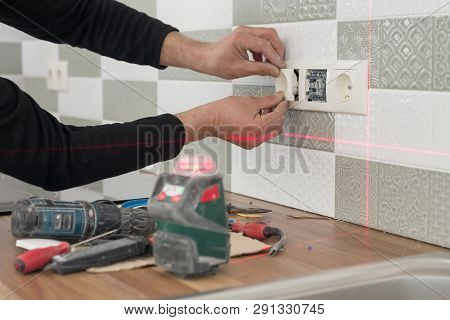 Electrician Using Infrared Laser Level To Install Electrical Outlets. Renovation And Construction In