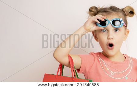 Portrait Of An Excited Beautiful Little Child Girl Wearing Dress And Sunglasses Holding Shopping Bag