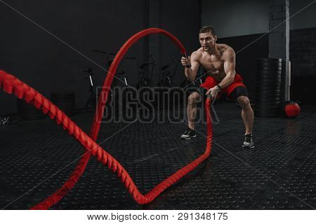 Battle Ropes Exercise During Atlete Training At The Workout Gym. Man Training With Rope. The Sport M