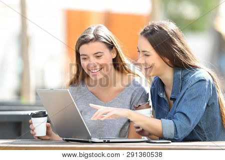 Two Happy Friends Checking Online Content On Laptop Sitting In A Park