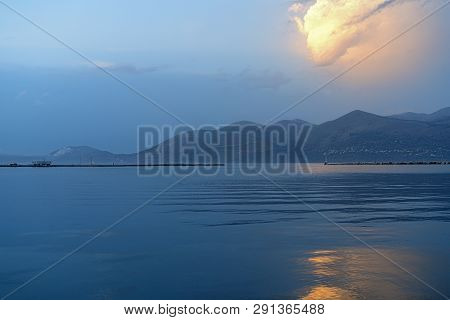 Ocean Landscape With An Orange Glowing Cloud Above A Mountain Range