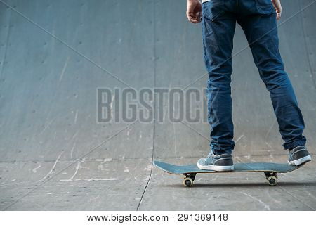 Urban Skater. Leisure And Lifestyle. Man On Skateboard. Guy In Jeans Backview. Cropped Shot. Skate P
