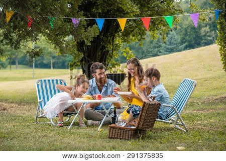 Dedicated young parents of two children listening to their funny son talking while eating together during family picnic in a summer day
