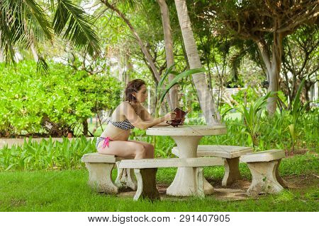A Woman Reading A Book In The Garden With Stone Furniture.