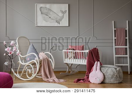 Flowers And Rocking Chair In Grey Baby's Bedroom Interior With Poster And Pouf. Real Photo