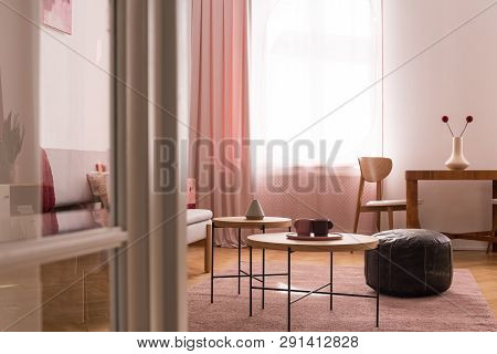 Two Coffee Cups On Wooden Coffee Table In Chic Pastel Pink Living Room With Oldschool Leather Pouf O