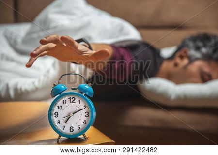 Close Up View Of A Sleepy Guy Trying To Snooze A Vintage Clock