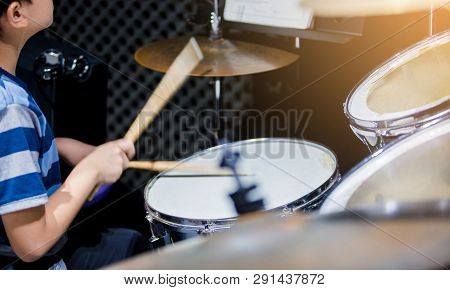Blurry Image Of Wooden Drumsticks In Hands Of Asian Kid Wearing Blue Striped T-shirts To Learning An