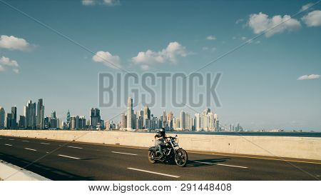 Man Riding Motorcycle In Panama City With Skyline In Background