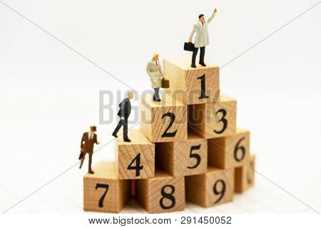 Miniature People: Business People Standing On Wooden Box With Top Of Ranking. Business Career Growth