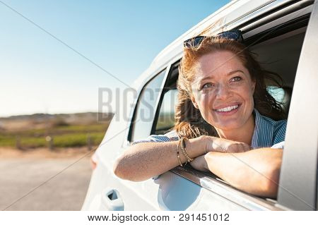 Smiling young woman peeking out of car window. Cheerful girl enjoying breeze from running car. Mature woman with red hair in the wind leans out of the car window and looking straight with copy space.