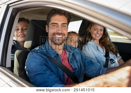 Smiling young family with two children sitting in car and driving. Family relaxing during road trip while looking at camera. Portrait of happy father riding in a car with wife, son and daughter.