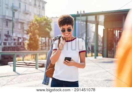 Smiling african woman using mobile phone while walking on street. Happy tourist searching for map directions on smartphone. Stylish brazilian girl wearing sunglasses looking at cellphone.
