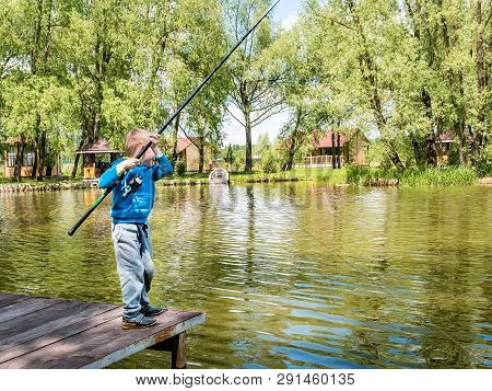 Boy Fishing From A Wooden Dock On A Lake Or Pond Pier In A Sunny Summer Day. Back View Of A Little 5