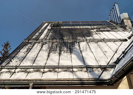 Tin Roof On Which Lies The Snow, Visible Facade Of The Building, Gutter, Ventilation Chimneys And An