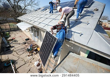 Male Team Workers Installing Stand-alone Solar Photovoltaic Panel System. Electricians Lifting Blue