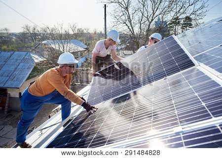 Male Workers Installing Solar Photovoltaic Panel System. Electricians Mounting Blue Solar Module On