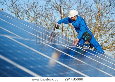 Man Engineer In Blue Suit And Protective Helmet Installing Stand-alone Solar Photovoltaic Panel Syst