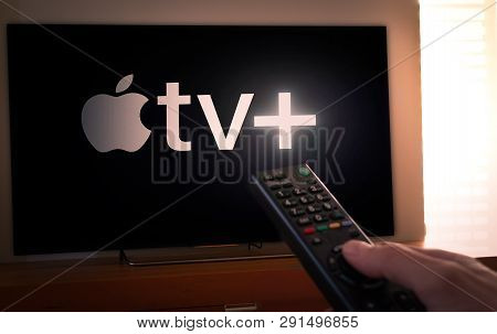 Barcelona, Spain. March 2019: Man Holds A Remote Control With The New Apple Tv+ Screen On Tv. Apple
