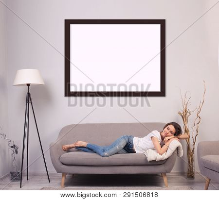 Portrait Of A Beautiful Smiling Young Woman Lying On A Sofa. Girl Wearing White Tshirt And Blue Jean