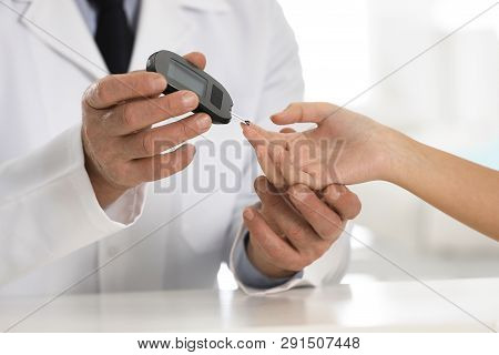 Doctor Checking Patient's Blood Sugar Level With Digital Glucometer At Table, Closeup. Diabetes Cont