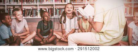 Teacher teaching kids in library at elementary school