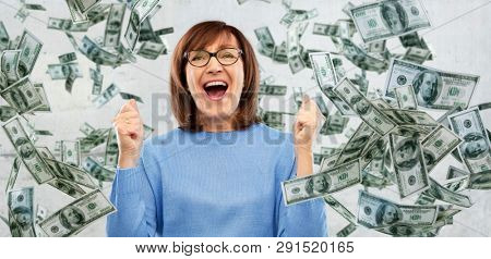 success, jackpot and finances people concept - happy laughing senior woman in glasses celebrating triumph under money falling from above over grey background