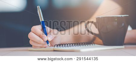 Woman Hand Is Writing On A Notepad With A Pen.