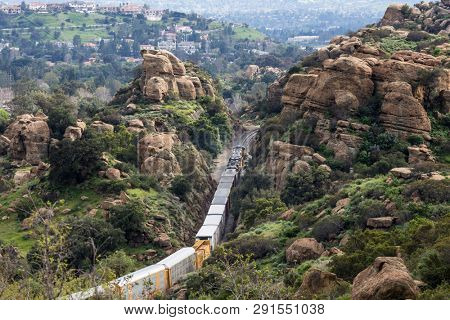 Los Angeles, California, USA - March 20, 2019:  Freight train passing rock formations and expensive San Fernando Valley homes in the Santa Susana Pass near Porter Ranch, Chatsworth and Simi Valley.